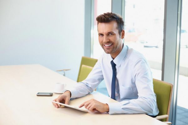 photodune-14415546-happy-businessman-at-modern-office-sitting-at-desk-with-digital-s
